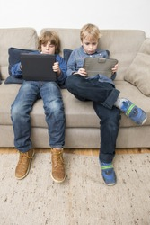 Two boys, playing games on electronic tablets, slouching on a couch, being bored, and acting individualistic
