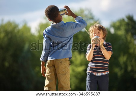 Two boys playing tin can telephone and having fun at the park