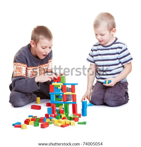 Two boys playing together with many building bricks