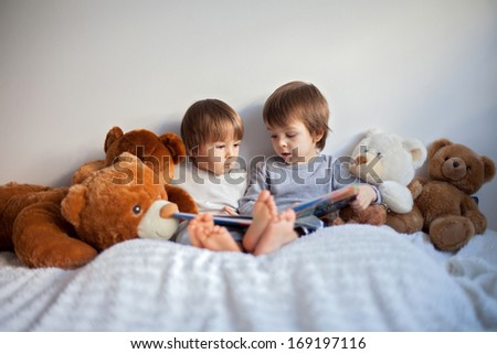 Two boys reading a book educating themselves