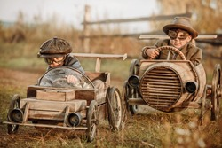 Two boys, riders compete against each other on homemade wooden car on rural road. Retouch for retro