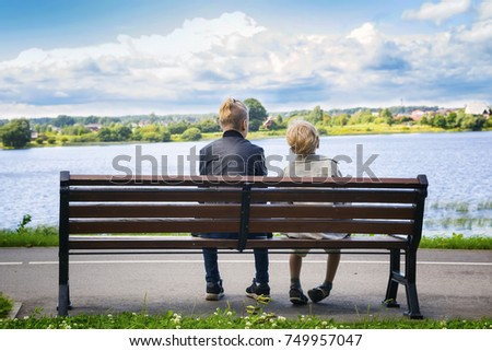 Two boys sit on a bench  by the river in the  park