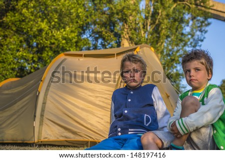 two boys sitting in front of a tent, looking at the sunset