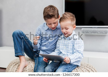 Two boys sitting in the living room using a tablet pc
