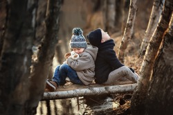 Two boys sitting on a wooden bridge in the stream in coat and jeans and embrace his beloved puppy