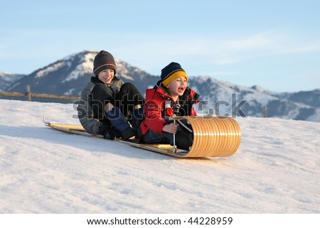 two boys sledding down a hill on a toboggan with excited expressions