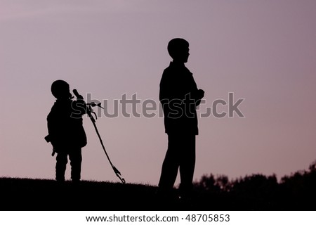 Two boys standing on a hill dark silhouette over evening sky