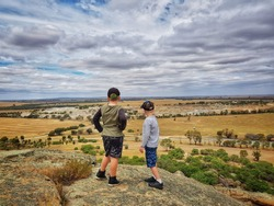 Two boys standing on edge of cliff looking at view of working quarry in the distance. Pyramid Hill, Victoria Australia.
