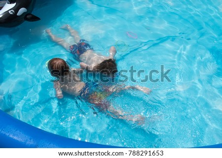 two boys swimming underwater in backyard swimming pool #788291653