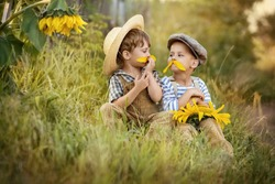 Two boys try on his mustache, made from the petals of a sunflower