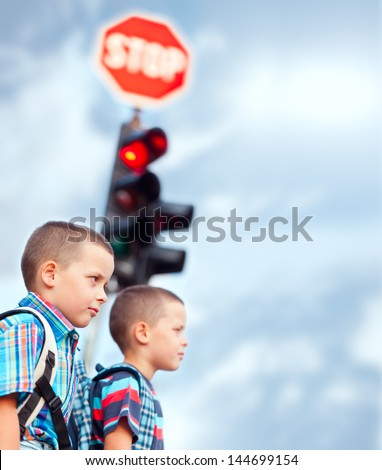 Two boys waiting to cross the street on their way to school.
