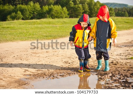 Two boys walking through a mud puddle in her rain coat and boots.