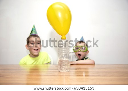 Two boys watching a chemistry experiment. children are surprised. Chemical reaction. the balloon is blow up when soda is added to a bottle of vinegar