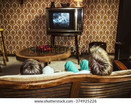 two boys watching television at ...