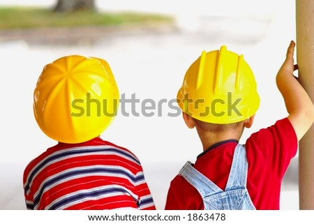 Two boys wearing hard hats viewed from behind