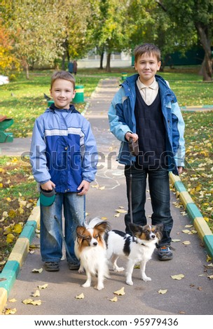 Two boys with dogs in autumn park