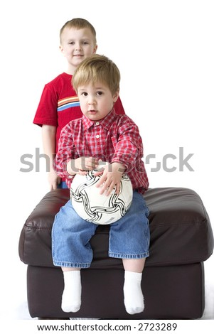 Two boys with soccer ball on white