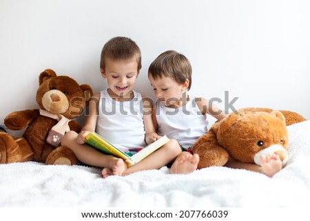 Two boys with teddy bears around reading a book educating themselves
