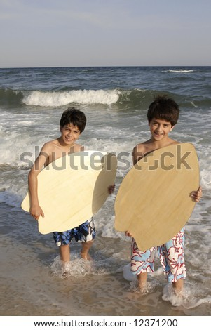 Two boys with their skimboards at the beach.