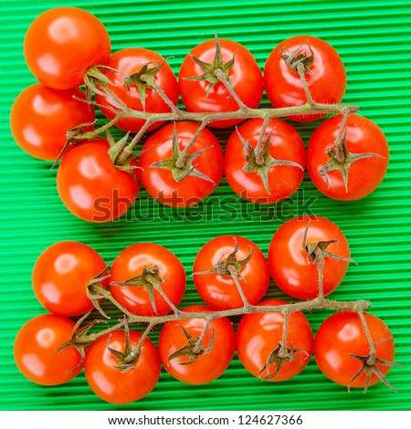 Two branches of red tomatoes on green tablecloth.