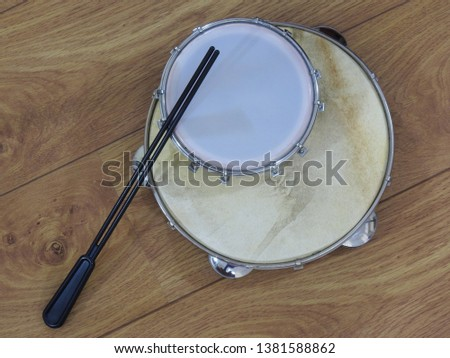 Two Brazilian percussion musical instruments: pandeiro (tambourine) and tamborim with drumstick on a wooden surface. The instruments are widely used to accompany samba music.
