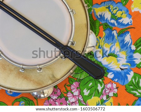 """Two Brazilian percussion musical instruments: pandeiro (tambourine) and tamborim with drumstick, on a colorful """"chitao"""" fabric with large floral prints. They are widely used in samba ensembles."""
