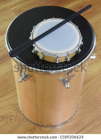 """Two Brazilian percussion musical instruments: tamborim with drumstick and """"tantan"""" (or """"rebolo"""") on a wooden surface. They are used in samba and pagode ensembles, two Brazilian rhythms. Top view."""