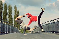 Two breakdancers dancing breakdance on the street