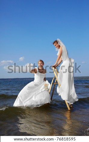 two brides on stepladder in sea waters