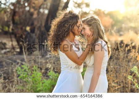 two brides white dresses looking one on each other. close face to face. background at the forest. Stockfoto ©