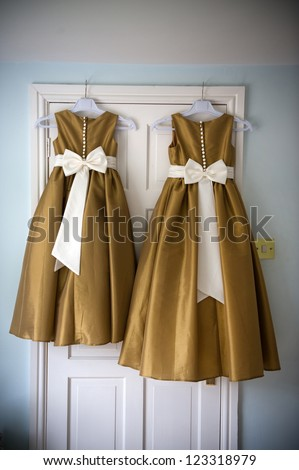 two bridesmaids dresses on hangers before a wedding
