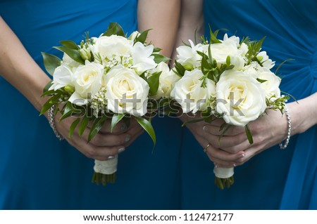 two bridesmaids in blue holding wedding bouquets of white roses
