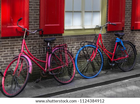 Two bright bright bikes near the wall of the house, bright bright background, healthy lifestyle #1124384912
