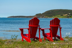 Two bright empty red adirondack chairs on the edge of a green grassy meadow overlooking the blue ocean with mountains covered in trees, a bay and cove. The water is calm and the sky is blue.