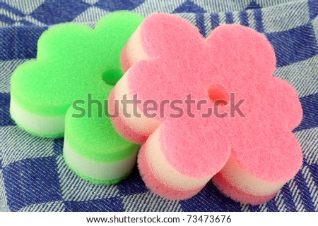 two brightly colored abrasive pads on a blue and white checkered kitchen towel