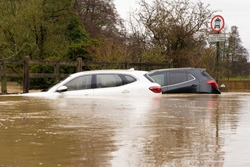 Two broken down cars submerged in a flooded ford after heavy rain. December 2020. Much Hadham, Hertfordshire. UK