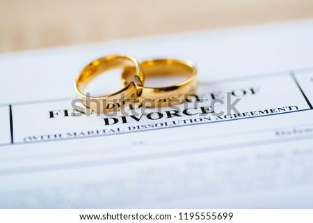 Two broken golden wedding rings divorce decree document. Divorce and separation concept #1195555699