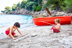 Two bropthers are playing together with bamboo at the seaside on the beach. Siblings sitting on the sand near red rowboat. Children enjoy summer holidays in europe seashore.