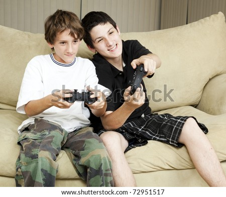 Two brothers at home playing video games together.