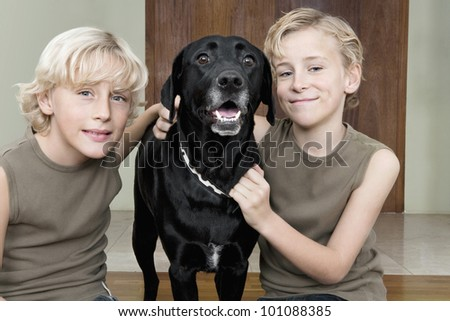 Two brothers at home proud of their pet dog.