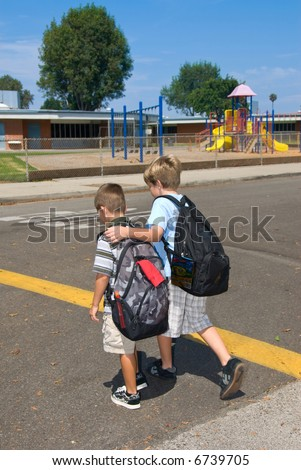 two brothers cross the street at a cross walk on their way to school