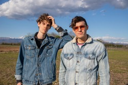Two brothers dressed in denim jackets pose in a field in the open air, brotherhood concept.