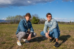 Two brothers dressed in denim jackets pose on a meadow squatting together. Brotherhood and friendship concept