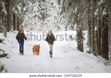 two brothers dressed in fur coats and jackets running with his dog on the winter snow-covered forest