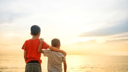 Two brothers enjoying sunset view at the seaside. Additional grains effect to create mood.