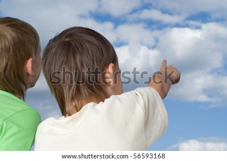 two brothers look to the sky with clouds