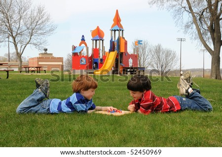 Two brothers play Chinese checkers in the park
