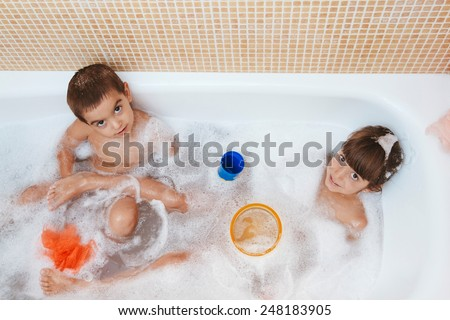 Two brothers playing in the bath together