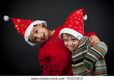 Two Brothers playing together with christmas hat on black background.