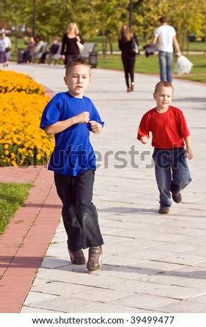 Two brothers run on pathes of city park